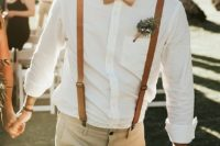 a light summer groom's look with a white shirt, amber leather suspenders, tan pants and a greenery boutonniere