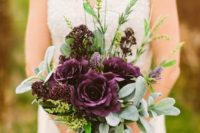 a moody fall wedding bouquet with greenery and deep purple roses and blooms