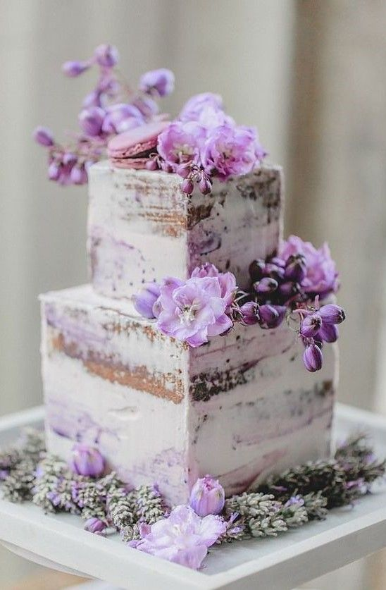 a naked wedding cake decorated with purple blooms and topped with a purple macaron