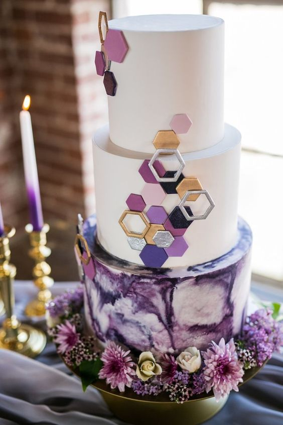 a purple and metallic wedding cake with hexagons and a marble effect