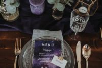 a purple nd grey wedding tablescape with purple candles, blooms and menus and calmer grey shades