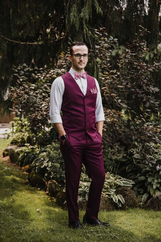 a purple suit with a waistcoat, a white shirt and a pink bow tie for a whimsical and statement groom's look