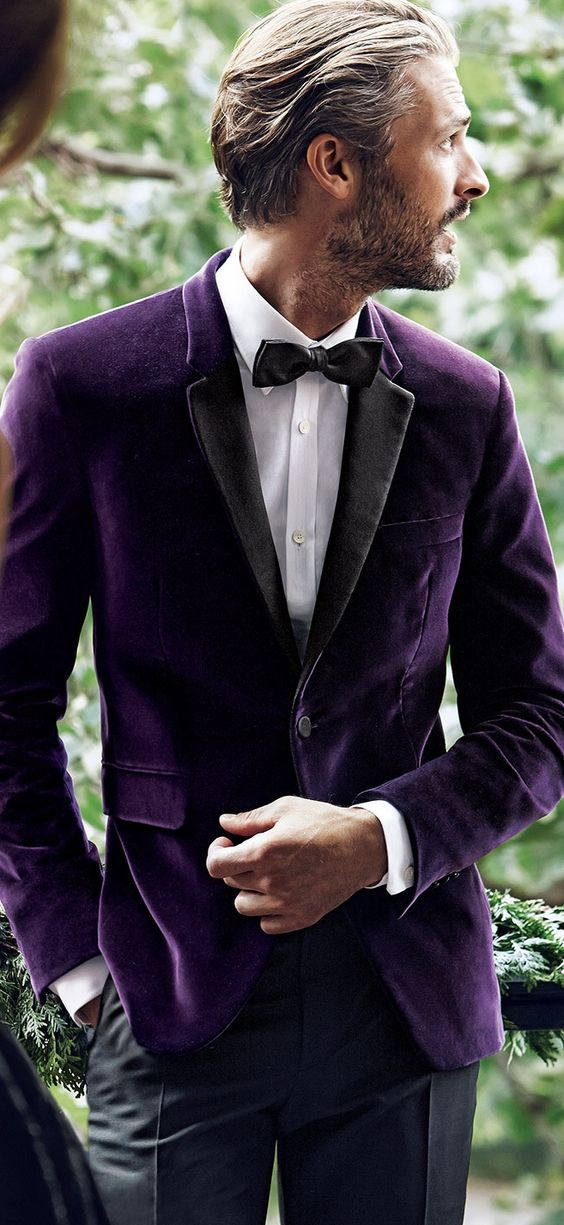 a purple velvet tux with black lapels is a refined and chic groom's outfit idea