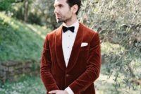 a rust vevlet blazer, a white shirt, a black bow tie and black pants for a bold and chic fall groom's look