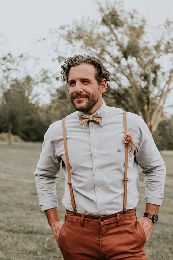 a rustic groom's look with an off-white shirt, terracotta pants, amber leather suspenders and a printed bow tie