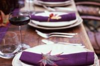 a rustic wedidng tablescape with a purple table runner, napkins and fall leaves