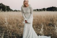 a sheath silver wedding dress with bell sleeves and a train for a super glam and catchy look