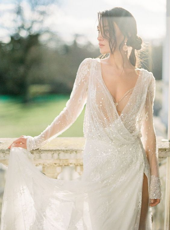 a shiny white wrap wedding dress with a deep neckline, long sleeves and a thihg high slit