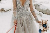 a silver wedding ballgown with a depe neckline, long sleeves and statement snowflake earrings for a winter bride