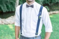 a simple groom's outfit with a white shirt, grey pants, navy suspenders and a printed bow tie for a bolder look