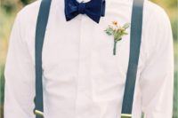 a simple summer outfit with tan pants, blue suspenders, a navy velvet bow tie and a bright boutonniere