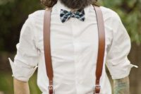 a stylish outfit with a white shirt, wide brown leather suspenders, a matching belt, a printed bow tie and tan pants