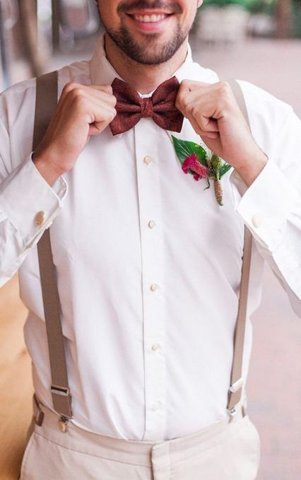 a summer groom's look with a white shirt, creamy pants, beige suspenders, a burgundy bow tie and a bright floral boutonniere