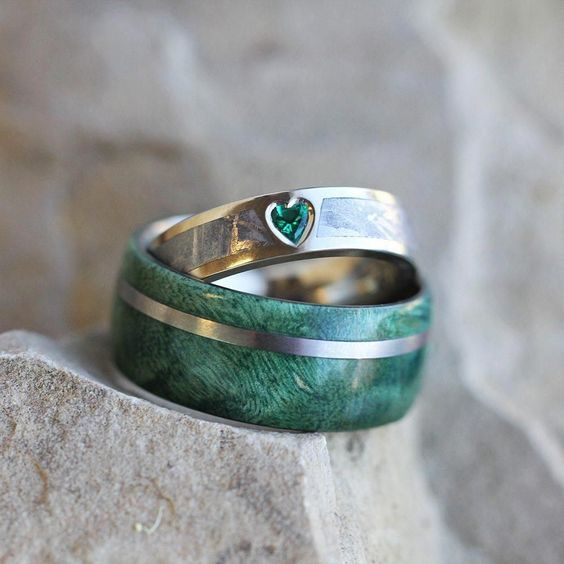 a titanium green box elder wood ring with an emerald and meteorite engagement ring in white gold