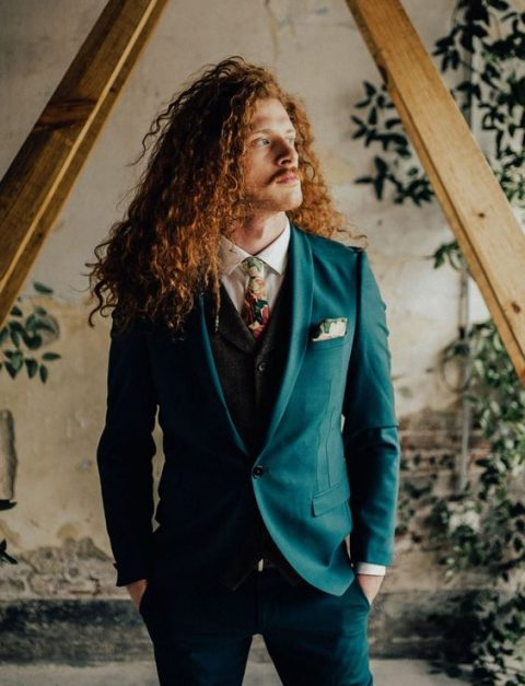 a turquoise suit, a black waistcoat and a white shirt with a floral tie plus long copper curls for a statement boho groom's look