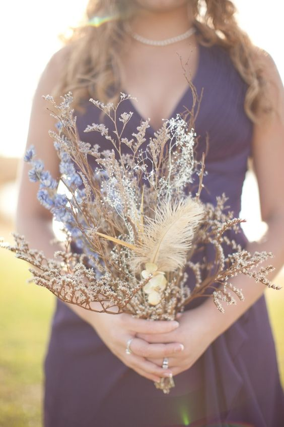 a wedding bouquet of dried herbs, feathers, blue blooms looks ethereal and unique