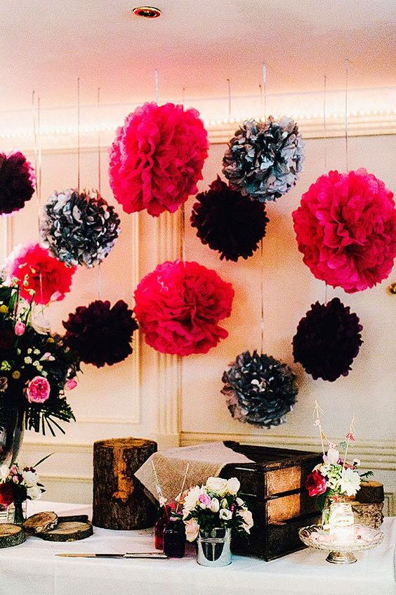 a wedding card table accented with fuchsia, black and black and white paper pompoms hanging over the table
