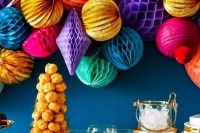 a wedding dessert table highlit with a super colorful honeycomb paper pompom wedding garland to make it feel fun