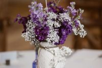 a white mason jar centrepiece with purple and white flowers and a burlap table number