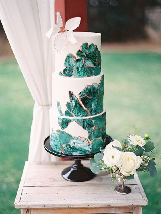a white wedding cake decorated with emerald agates with a copper edge is a bold modern idea