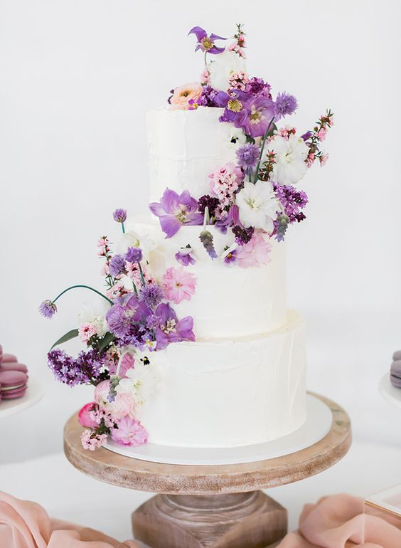 a white wedding cake topped with purple and blush blooms plus some leaves