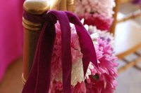 accent wedding chairs with pink and white paper pompoms on velvet ribbons to make them look cute
