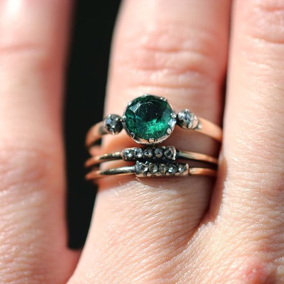 an emerald engagement ring with little diamonds is a gorgeous idea to rock and it looks amazing