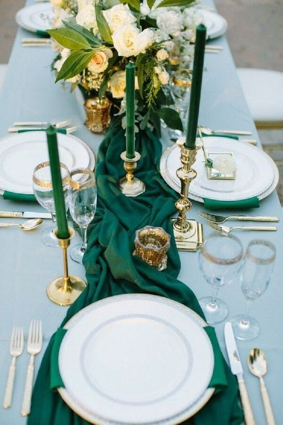 an emerald green table runner and matching candles plus gilded touches and a white bloom centerpiece