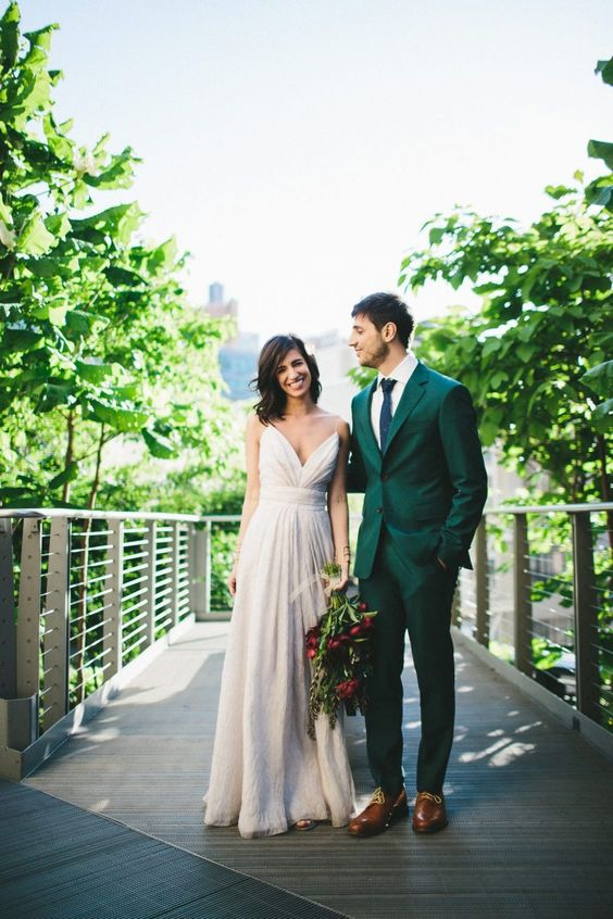 an emerald groom's suit paired with a navy tie, brown shoes and a white shirt for a bold modern look