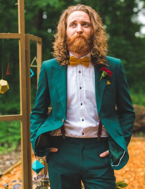 an emerald groom's suit with a mustard bow tie and a white shirt plus copper waves and a full beard for a bold look