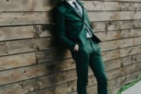an emerald suit, a black tie and brown shoes and colorful striped socks for a statement fall groom's look
