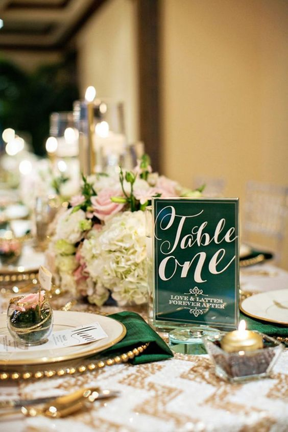 an emerald table number and a matching napkin paired with gold touches will give your tablescape a glam look