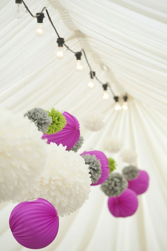 bright purple paper lamps, white, grey and green paper pompoms make the tent look fun and chic