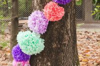 cover trees at the wedding with colorful pompom garland if you want to give the space a festival feel