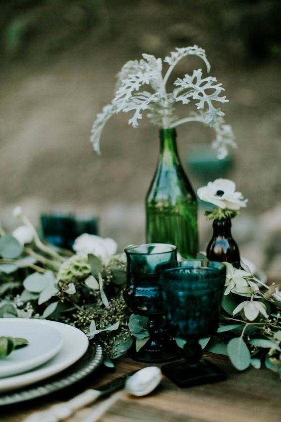emerald green glasses and a bottle for a centerpiece plus a lush eucalyptus wedding table runner