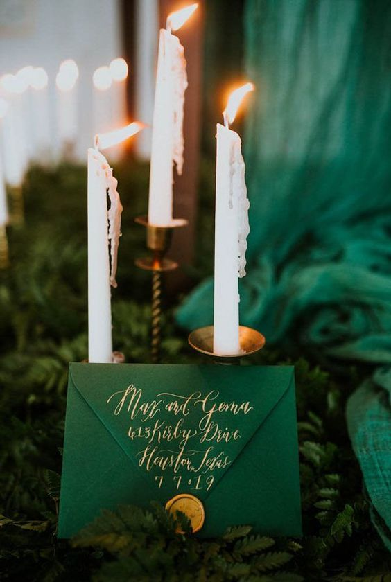 en emerald wedding invitation with gold touches placed in lush ferns on the table