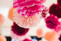 pink and peachy paper pompoms hanging over the space will add a chic feel and a bright touch to the venue