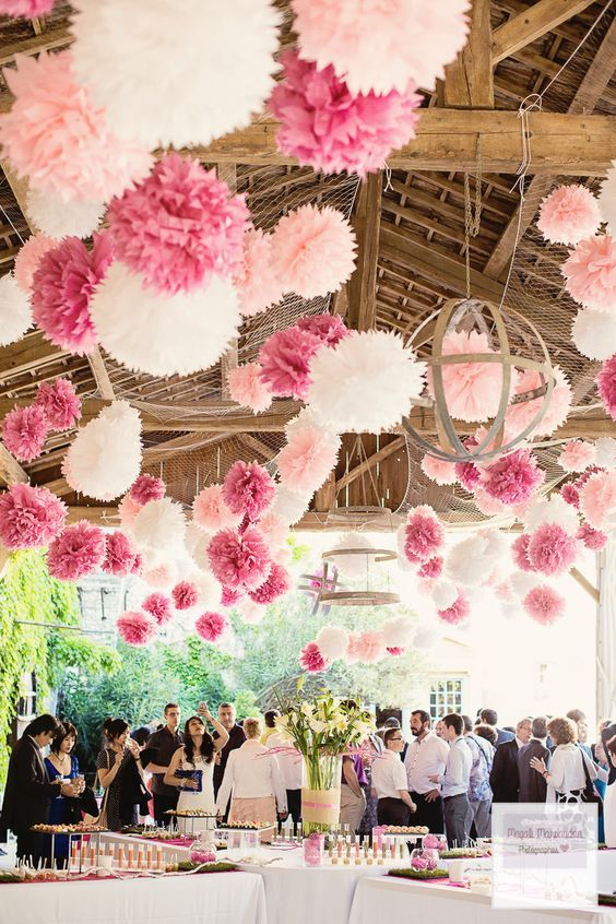pink, white and blush paper pompoms hanging over the reception space look fun and bright