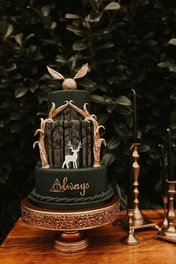 a HarryPotter-themed black wedding cake with gold letters, a Patronus, gold leaves and a gold Snitch cake topper is very dramatic