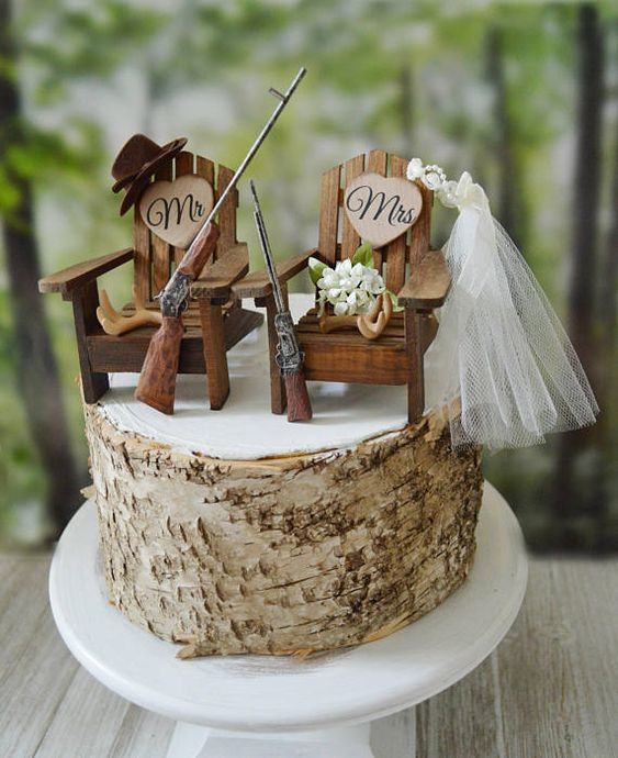 a birch bark wedding cake with wooden chairs, guns, antlers, a hat and a veil is a cool idea for a woodland wedding is a cool idea
