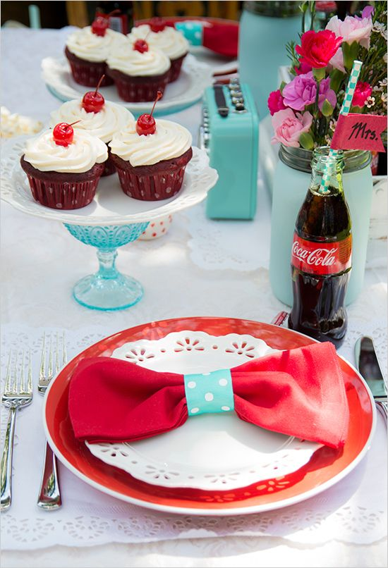 a blue, red and white wedding tablescape with bright plates, cupcakes and Coke in bottles