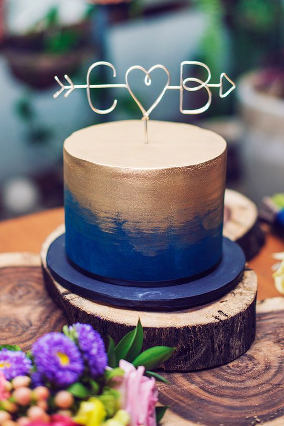 a bold blue and gold wedding cake with a cool wire topper is a fun and cheerful option