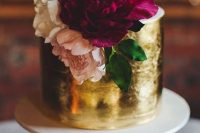 a bold wedding cake with a white and gold leaf tier and white, blush and purple blooms is very refined