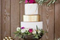 a bright and refined wedding cake with white and gold tiers, botanical patterns, bright blooms, white flowers and greenery
