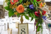 a bright and tall spring wedding centerpiece in pink, red, purple, white and yellow plus cascading greenery