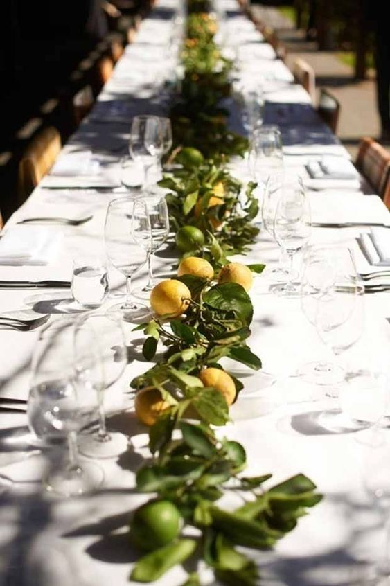 a bright citrus wedding table runner of lemons and limes and greenery is a very cool and summer-like idea