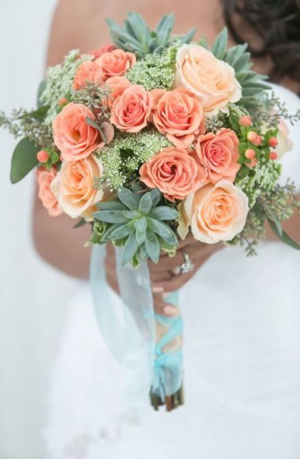 a bright coral and mint wedding bouquet with greenery and succulents is ideal for a bride