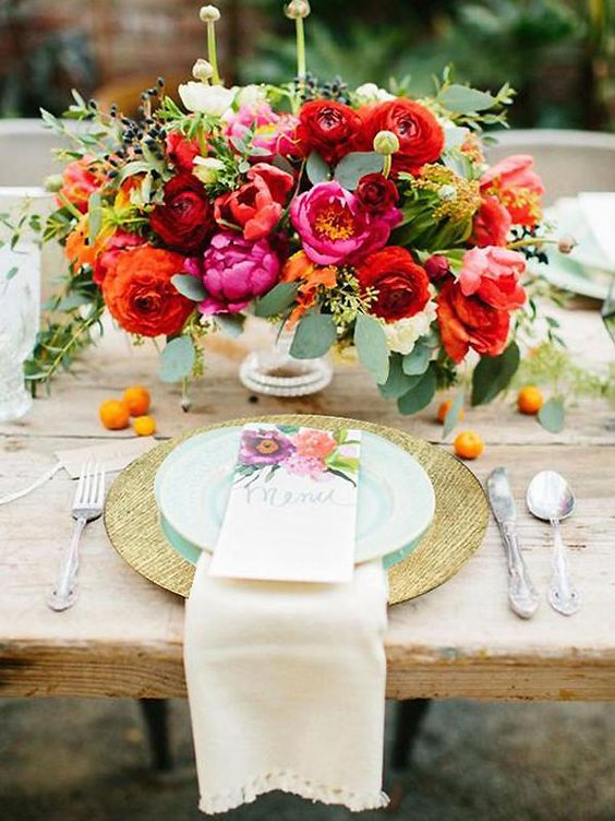 a bright floral wedding centerpiece in red, orange, fuchsia and some greenery plus privet berries