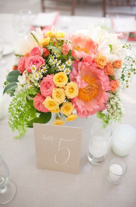 a bright sprign wedding centerpiece in pink, yellow, white and with much greenery looks cute