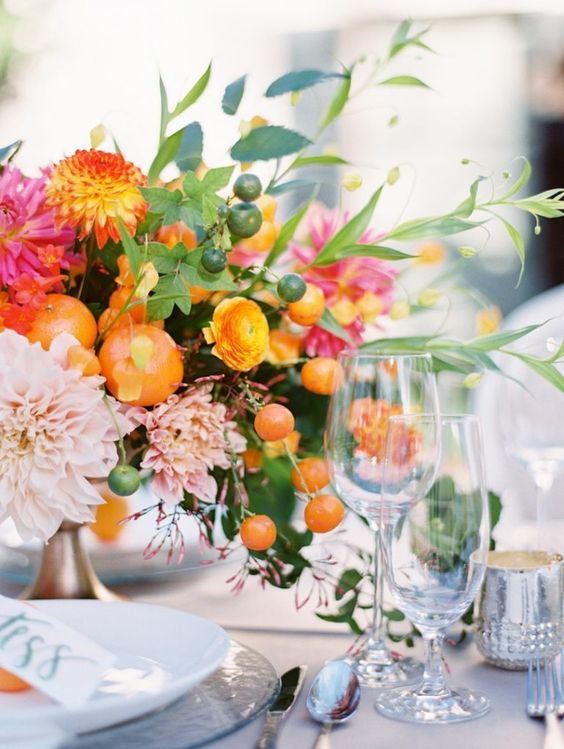 a bright spring wedding centerpiece in hot pink, marigold, blush and some citrus for a bold look